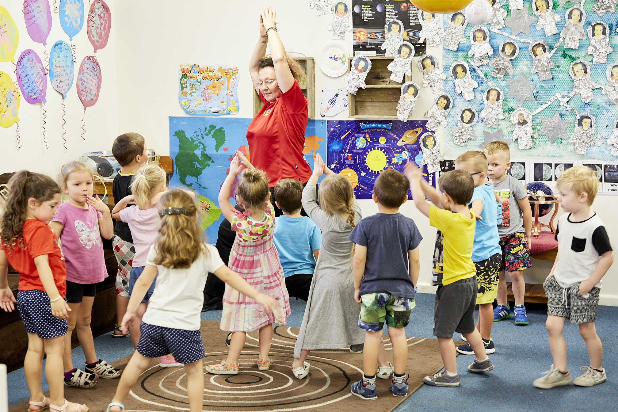 child care educator dancing with group of children in classroom