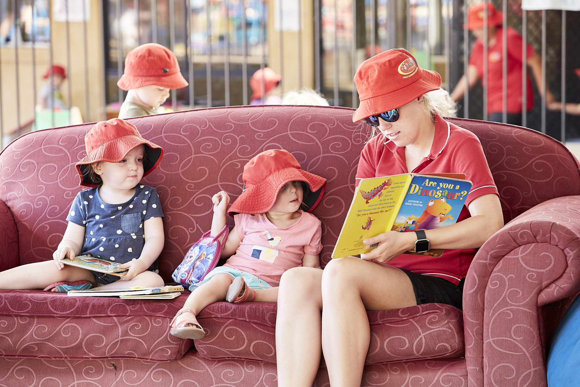 Child care educator reading to children on red couch